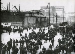 Treballadors sortint de les drassanes de Harland, el 1911, amb el Titanic al fons.